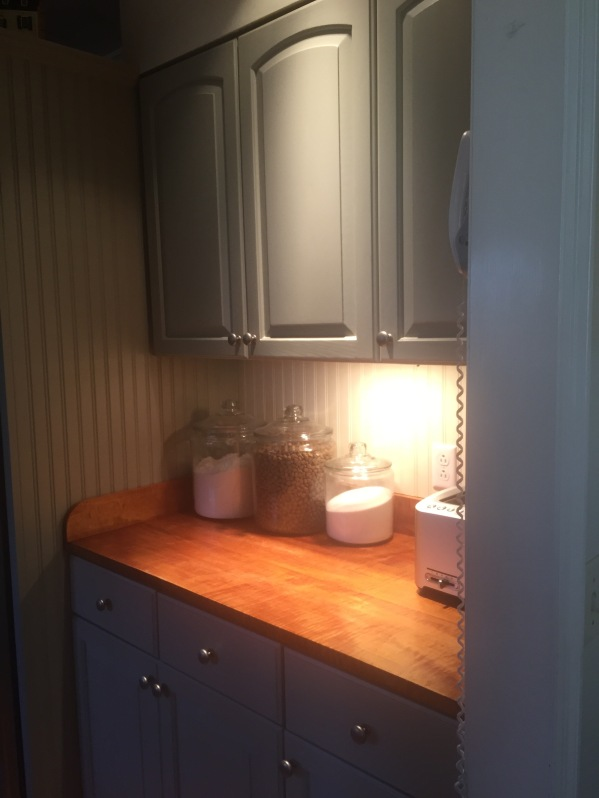 A kitchen corner: Benjamin Moore Historical Color #108—Sandy Hook Gray, with tiger maple counter.
