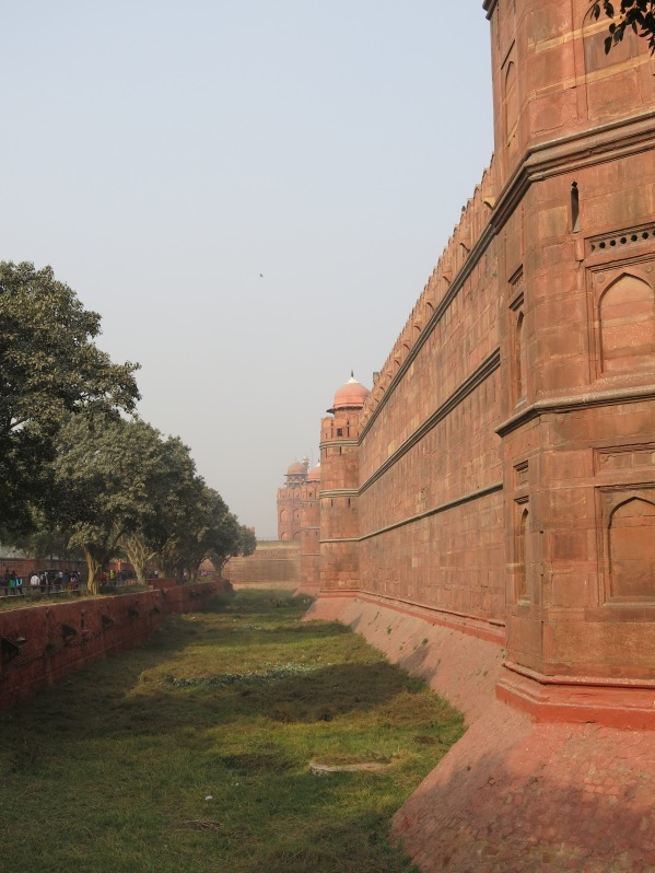 Approaching entrance gate along massive sandstone walls of Red Fort